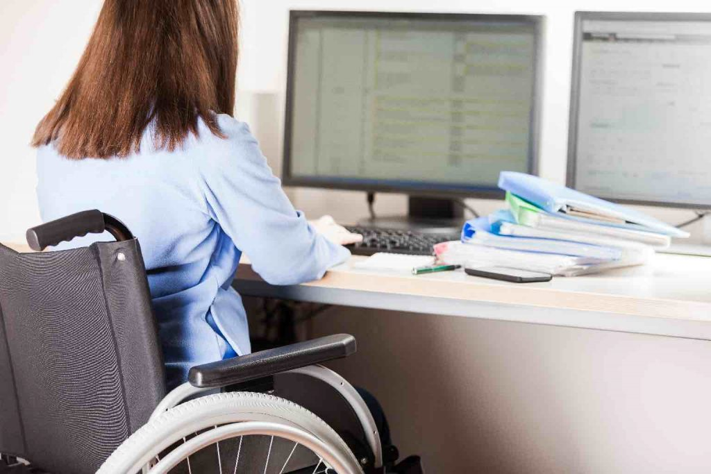 Young business woman person sitting wheelchair working office desk computer