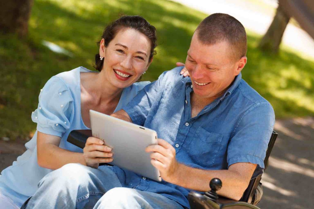 Man in wheelchair with his carer having fun while using tablet at the park