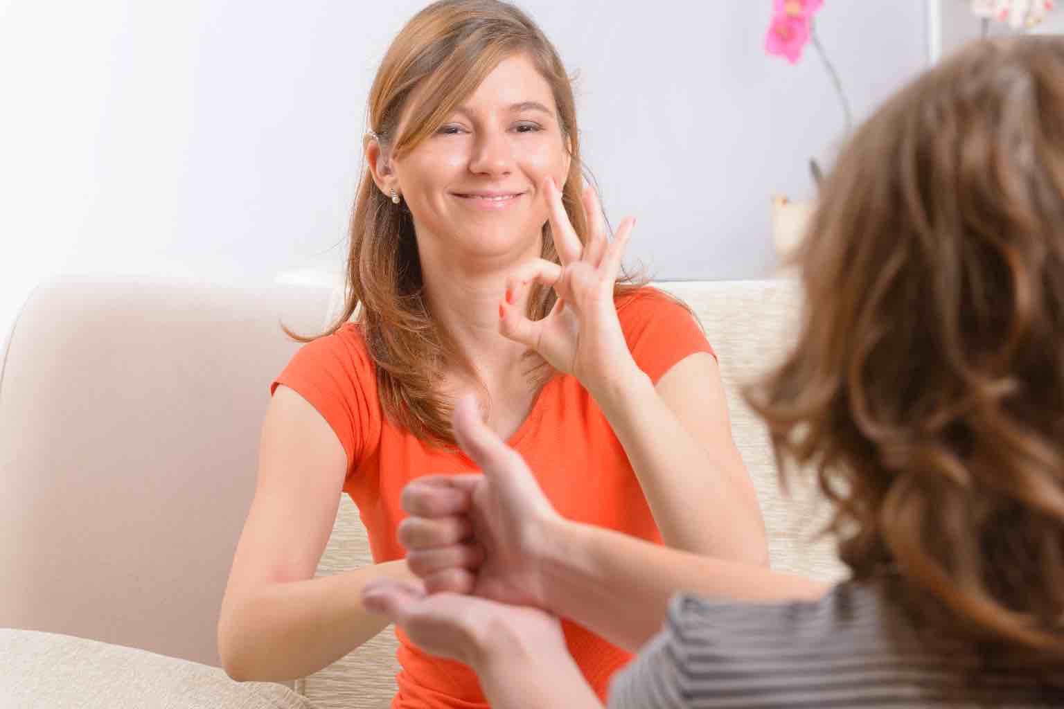 Two women conversing in a lounge room using sign language