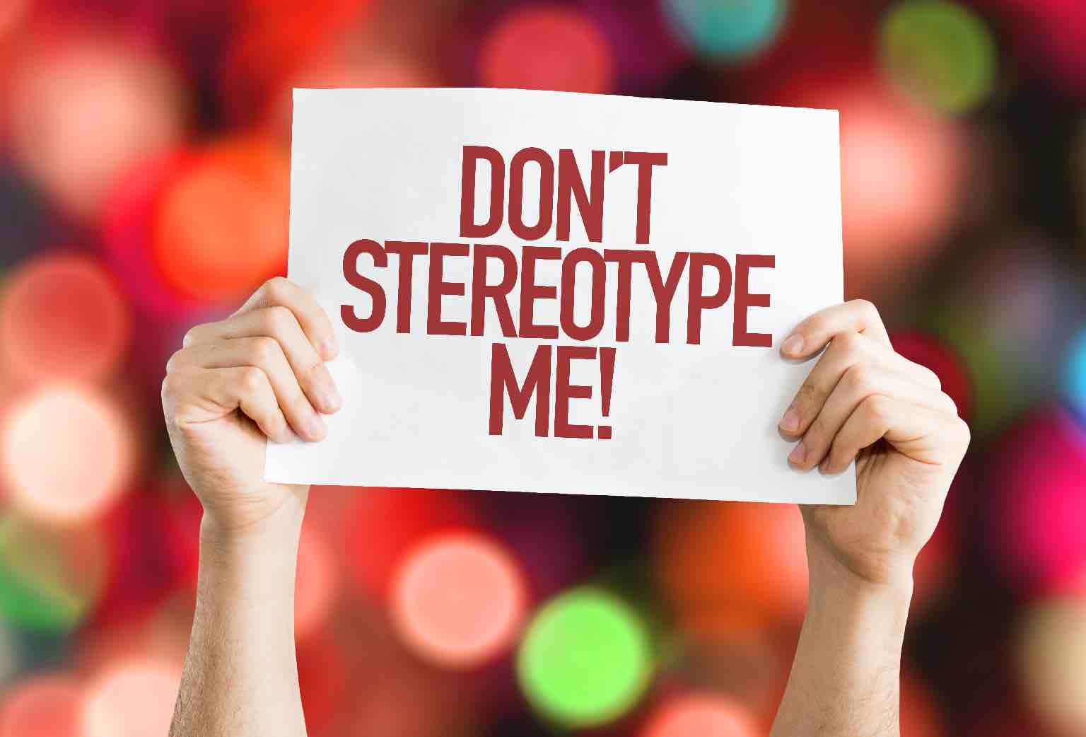 """A woman's hands/arms holding up a sign with the words """"Don't Stereotype Me"""" with bokeh background"""