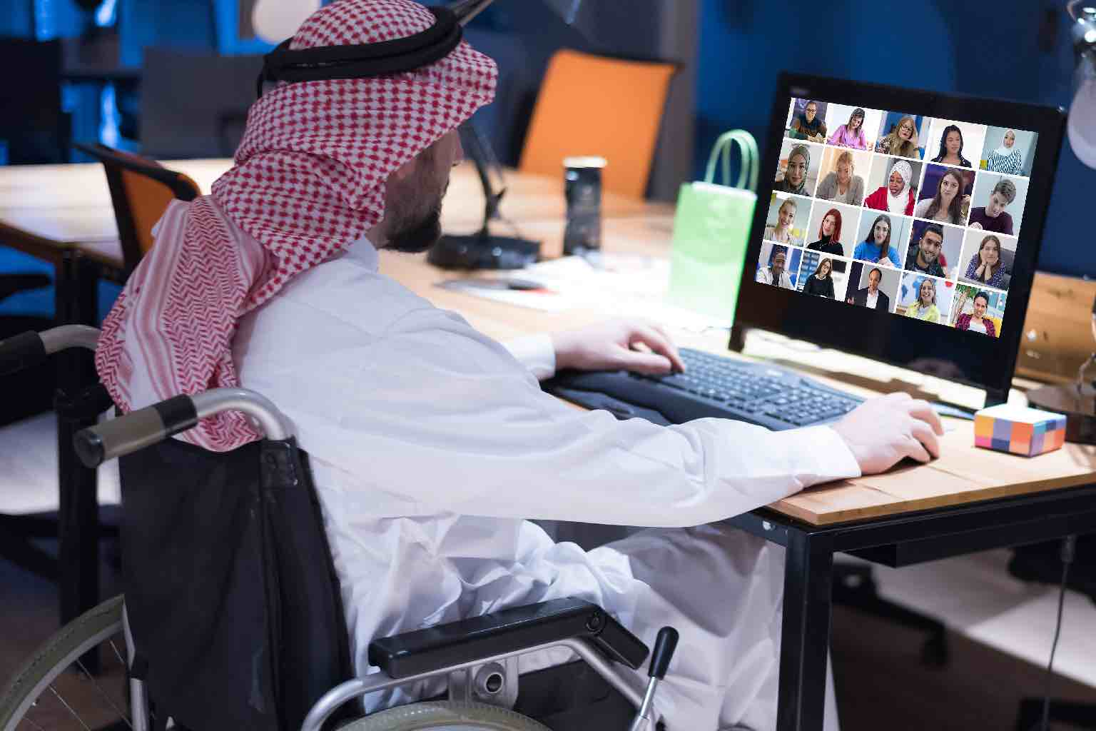 An Arabic man in a wheelchair in a traditional suit working in office on a video call.