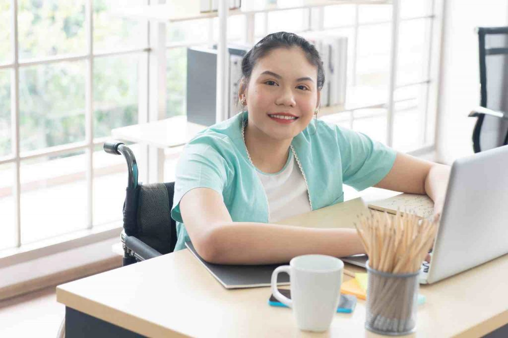 Young disabled Asian woman sits on a wheelchair using computer laptop for work at office workplace, look at the camera smiling,