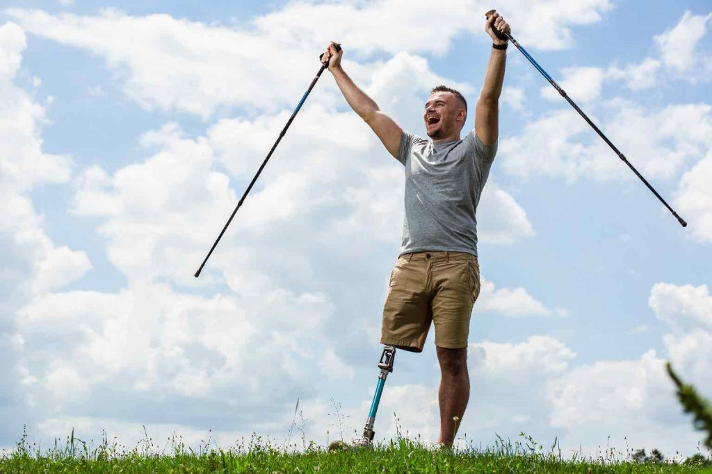 Happy pleasant man holding his hands up while enjoying Nordic walking sticks