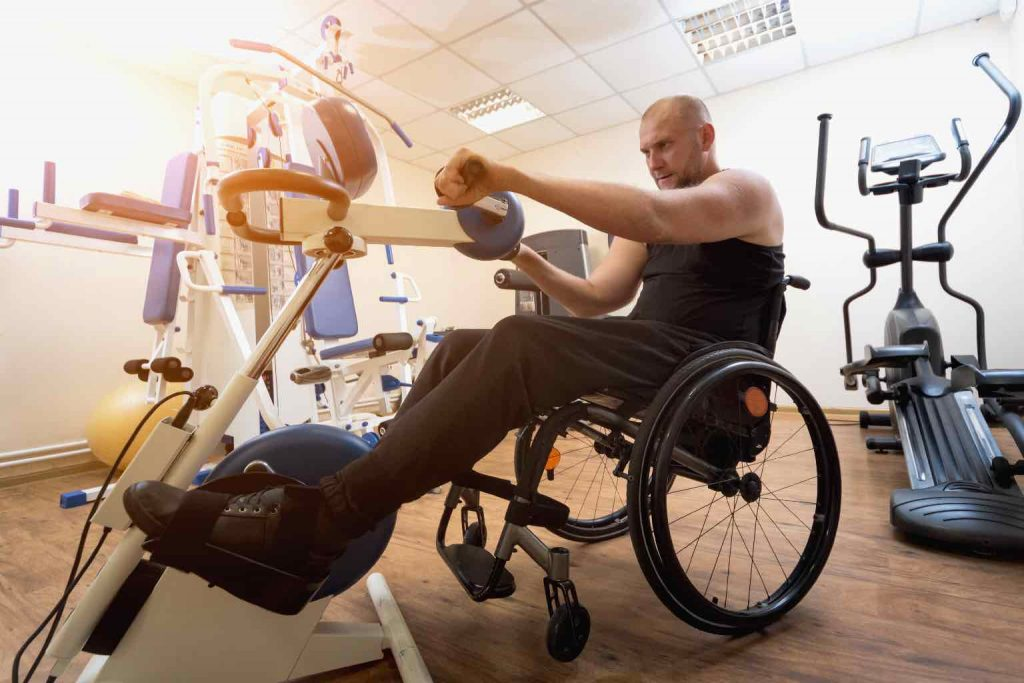 Man in a wheelchair training on specialist equipment in the gym.