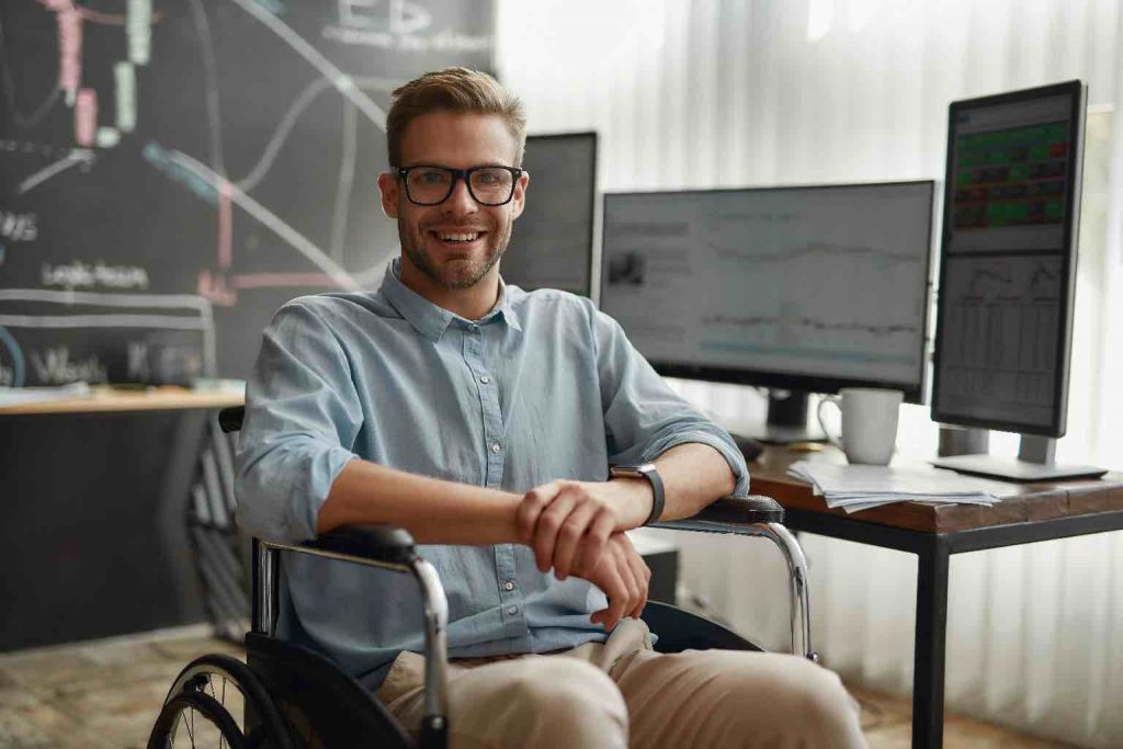 Young and positive male trader in a wheelchair smiling at camera while sitting at his workplace in the modern office. Disability and handicap concept. Handicapped worker. Trading online. Stock market