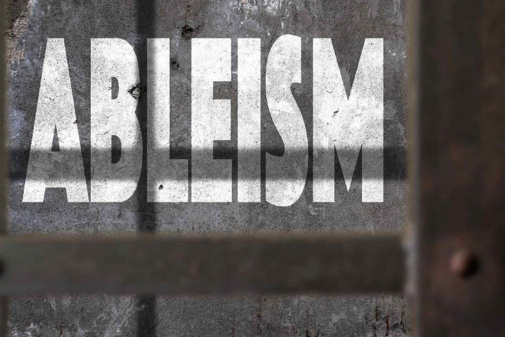 Ableism Written On A Wall With Jail Bars Shadow