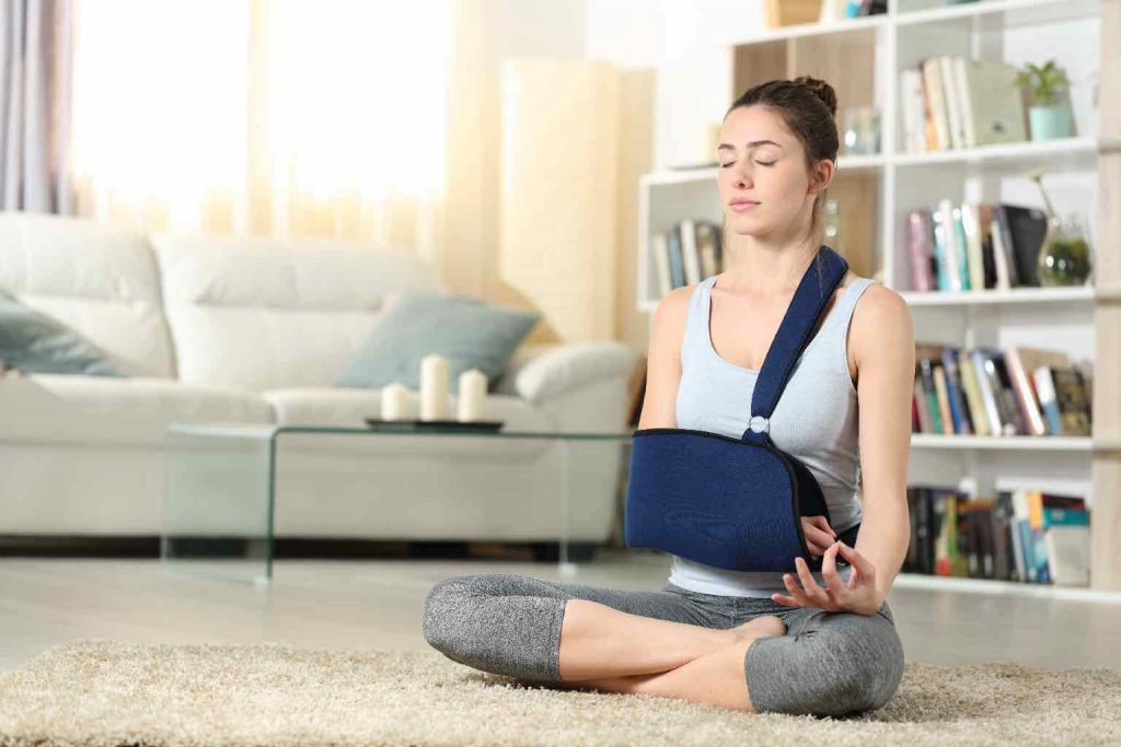 A woman with an arm in a sling, meditating in her living room