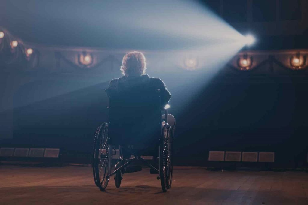 Aged man on wheelchair turning round and leaving stage in end of performance in theatre