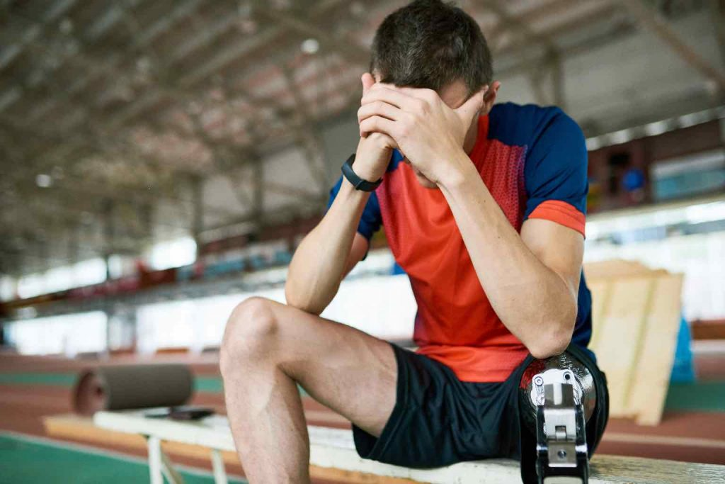 Portrait of young amputee athlete taking break from practice sitting on bench resting head on hands