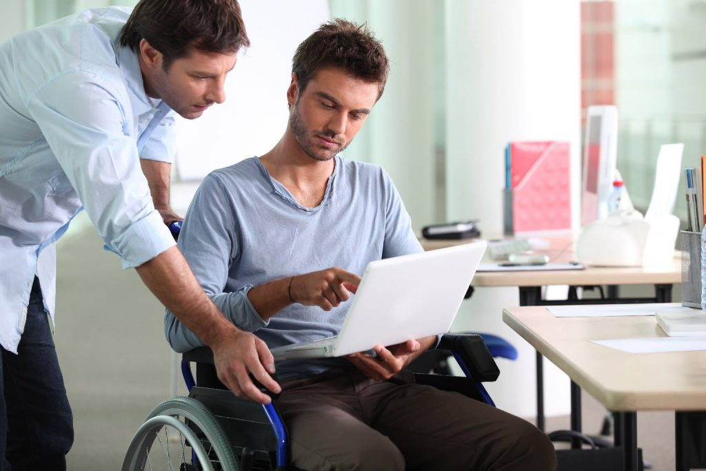 Businessman in wheelchair with laptop computer showing what's on the screen to a colleague