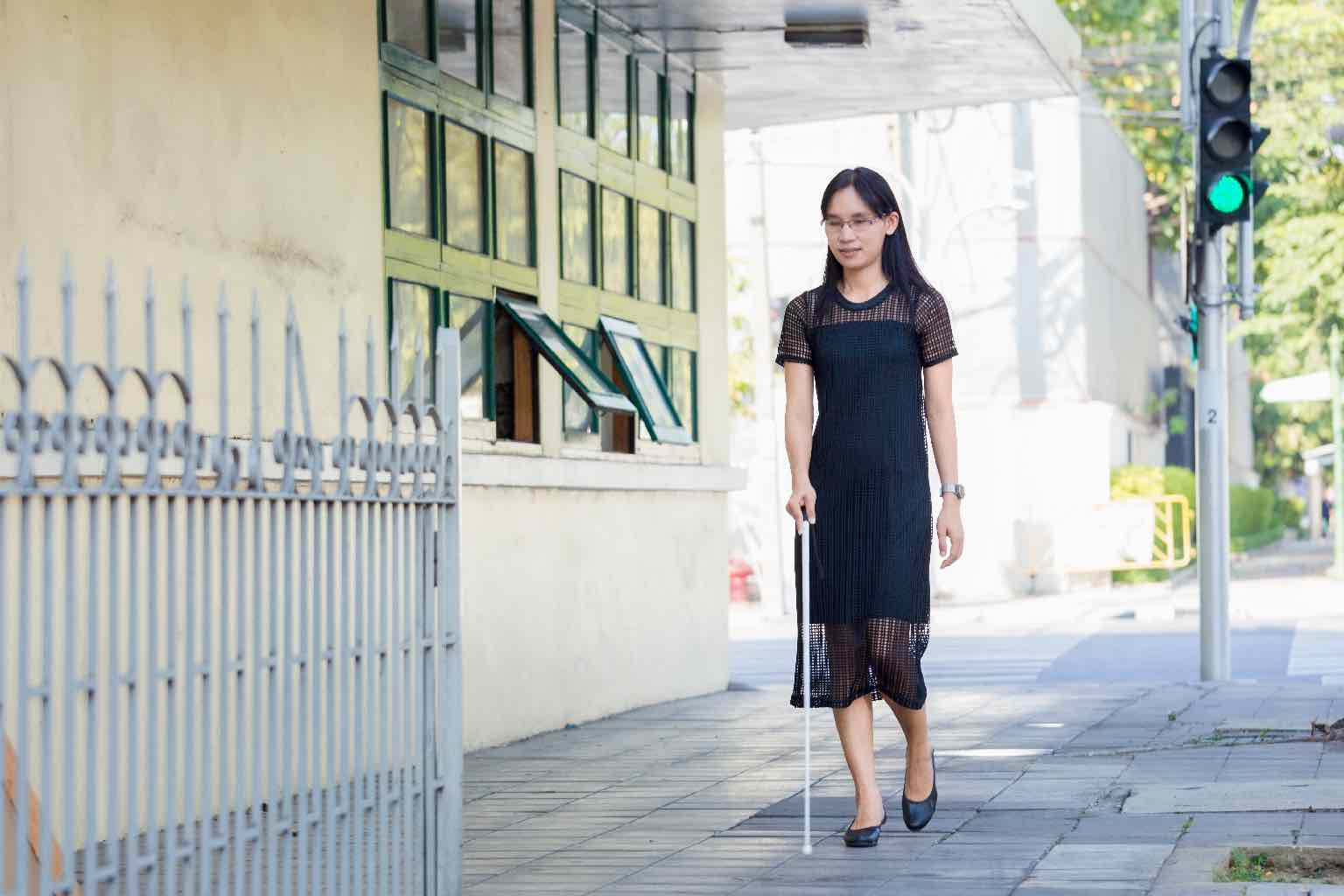 An Asian vision impaired woman walking along the street with a stick.