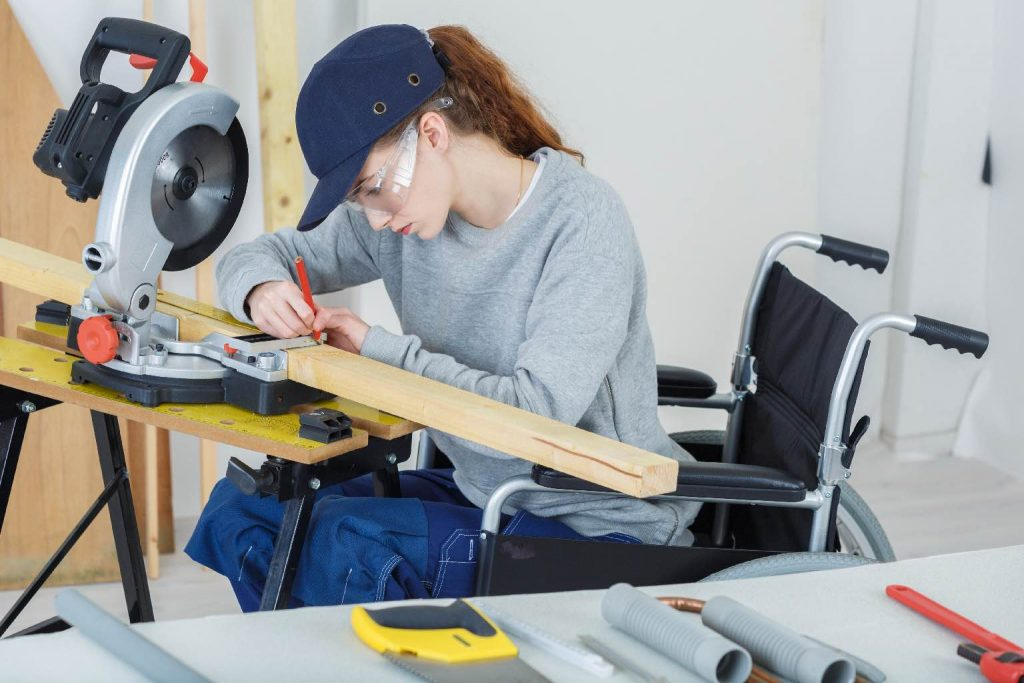 A woman in a wheelchair working on some wood.
