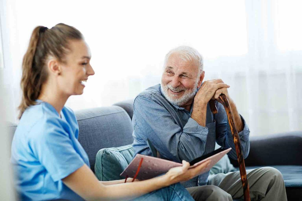 Doctor or nurse caregiver with senior man looking at photo album and picture at home