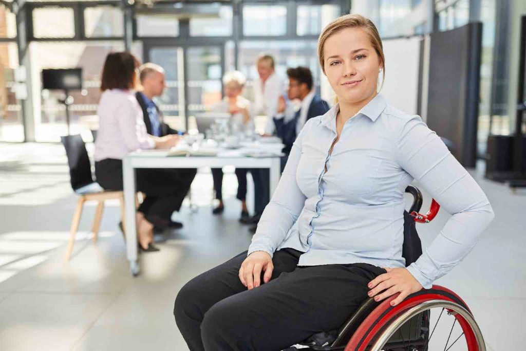 Proud businesswoman in a wheelchair in front of her team in a seminar or meeting