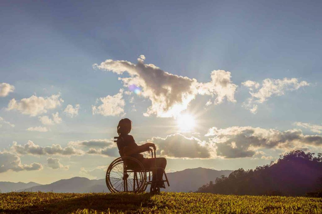A woman in a wheelchair out in nature under a mixed sky looking towards distant mountains