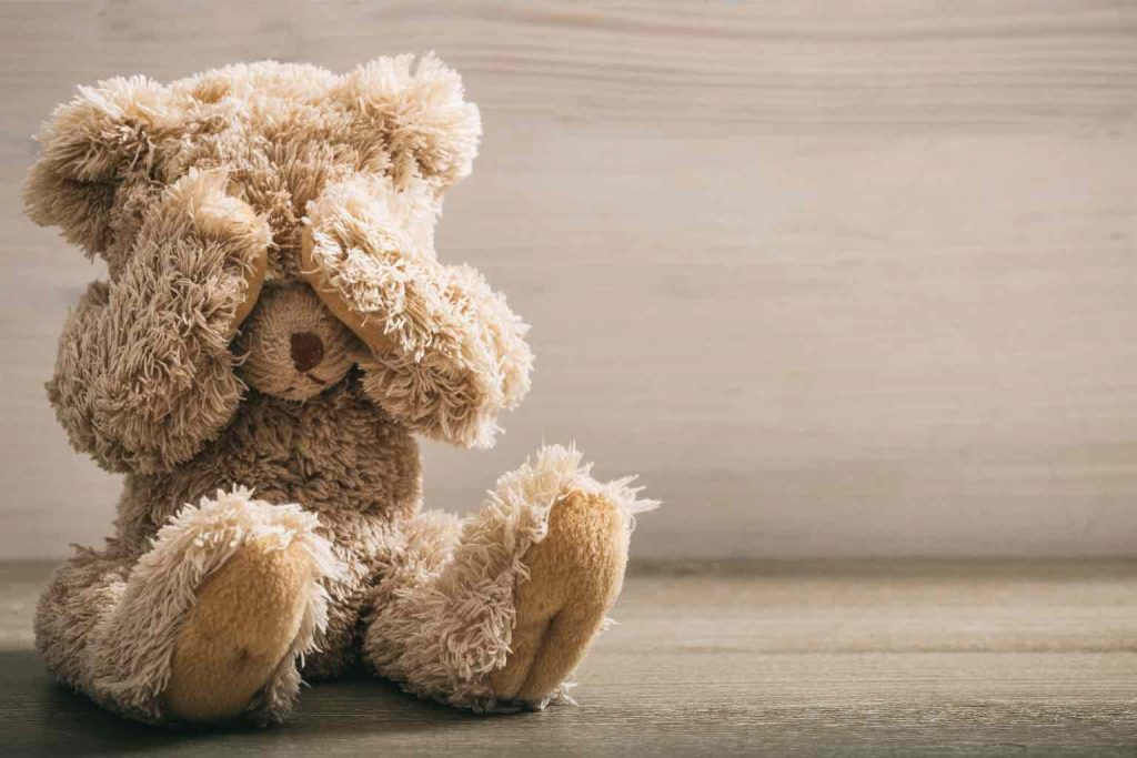 A stuffed teddybear weeping into his paws on the ground