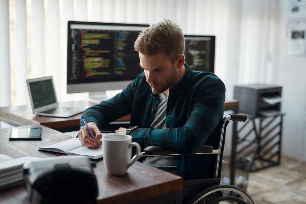 Young concentrated male web developer in a wheelchair making some notes while sitting at his workplace with multiple computer screens on the background. Focus on a man.