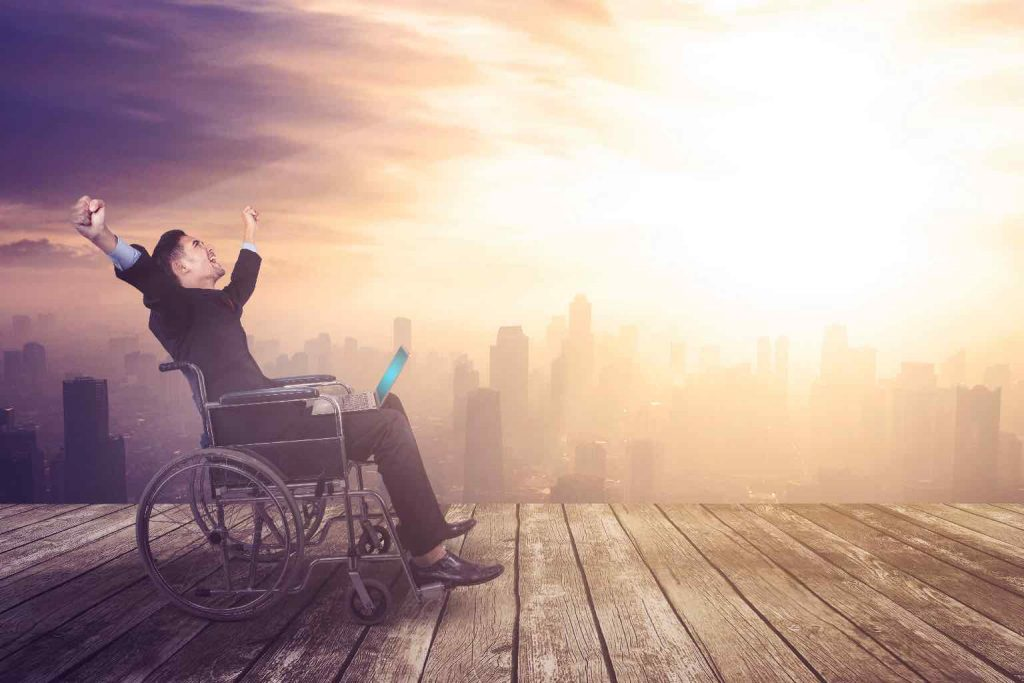 Disabled businessman celebrating his success while working with laptop on the building rooftop with sunrise background