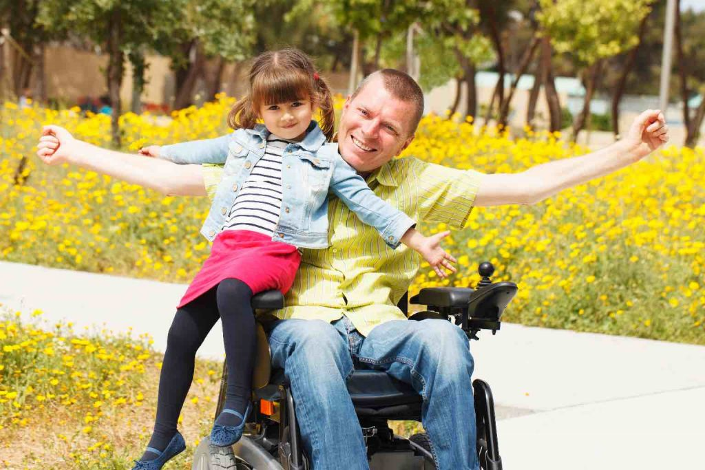 A young daughter with her father in a powered wheelchair, enjoying a park together