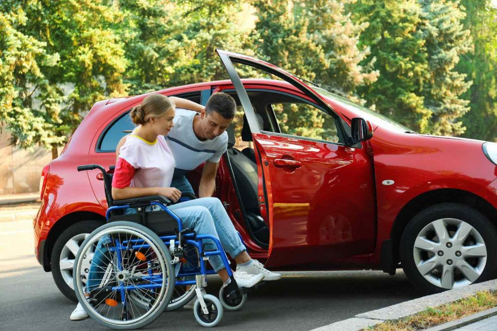 A young man helping disabled woman in wheelchair to get into car outdoors