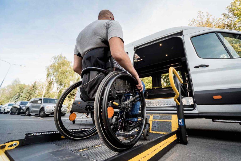 A man in a manual wheelchair entering a van via a ramp