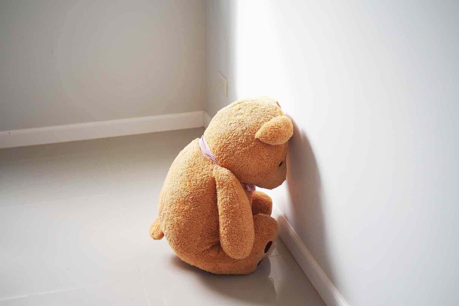 A cuddly toy teddy bear sitting leaning against the wall of the house alone, look sad and disappointed.