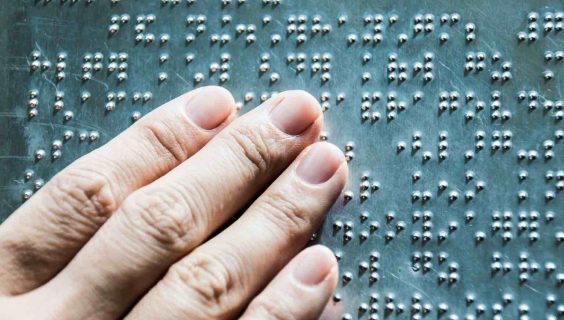 The fingers are touching the metal plate written in the Braille letters