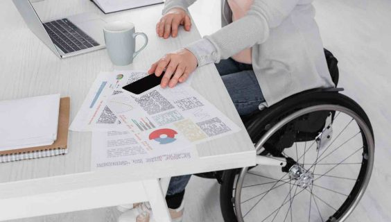 A woman in a wheelchair in an office picking up a smartphone.