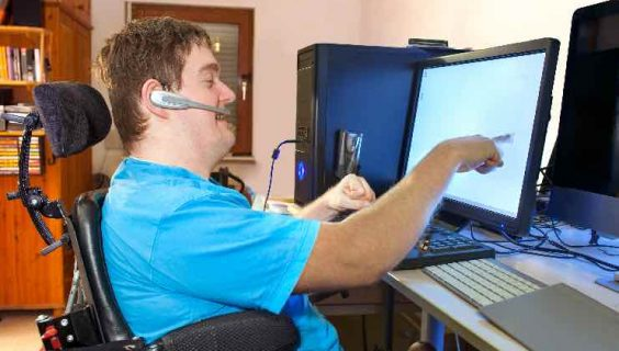 A man with Cerebral Palsy in a wheelchair, pointing at a computer screen.