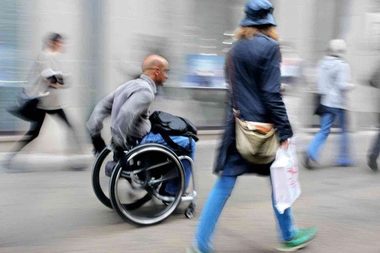 Blurred movement man in a wheelchair on a city street
