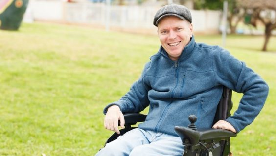 A grinning man with a cloth cap sitting in a powered wheelchair