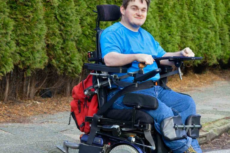 A young man with cerebral palsy in multifunctional wheelchair negotiating a mobile ramp on a kerb