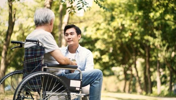 A young Asian man kneels in front of an older Asian man in a wheelchair, for a discussion