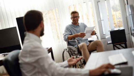 A man in a wheel chair chatting with a colleague.