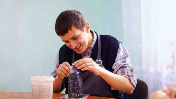 Man with a disability enjoying making a decoration.
