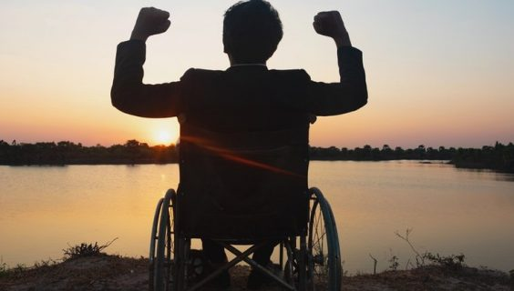 A silhouette of a man in a wheelchair beside a lake, fists raised in jubilation