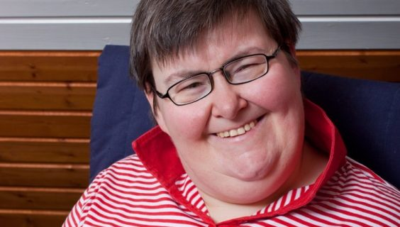 A smiling woman who lives with a mental disability looks up from reading to smile at us