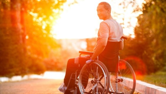 A man in a wheelchair looking back at us from a sun-filled sky
