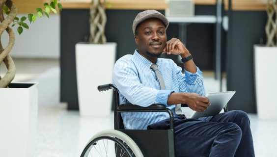 A smiling black man wearing a cloth hat in a wheelchair looking at us with a positive expression