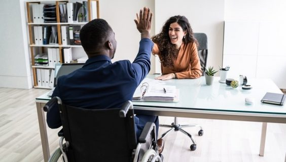 Disabled Businessman Giving High Five To His Smiling Female Partner In Office