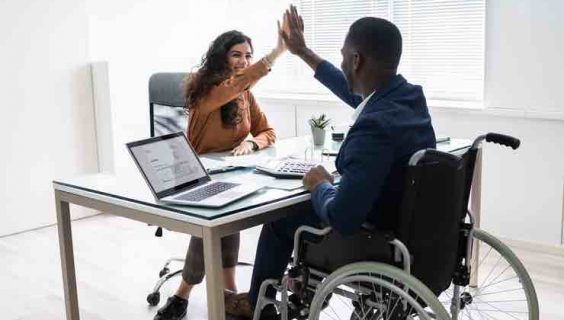 An African-American man in a wheelchair high fives a woman with a desk between them