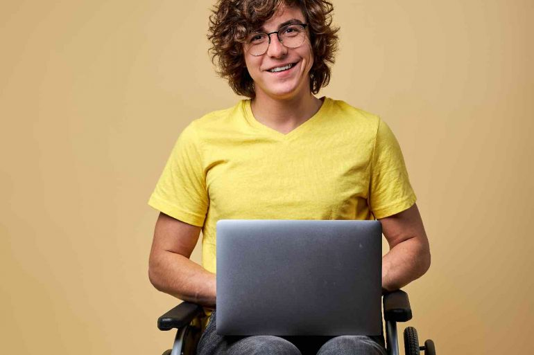 Disabled student preparing for exam using laptop, sitting in a wheelchair isolated in studio.