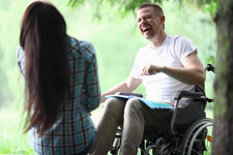 A man in a wheelchair laughing hard with a carer