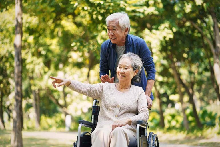 A senior women in a wheelchair and her partner strolling through a leafy park enjoying the scenery
