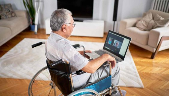 A white and grey-haired man in a wheelchair, participating in a video meeting on his laptop whilst seated in a living room.