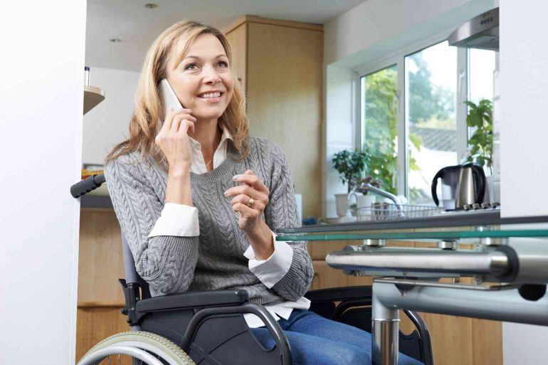 A smiling woman in a wheelchair talking on a mobile phone in a modern kitchen