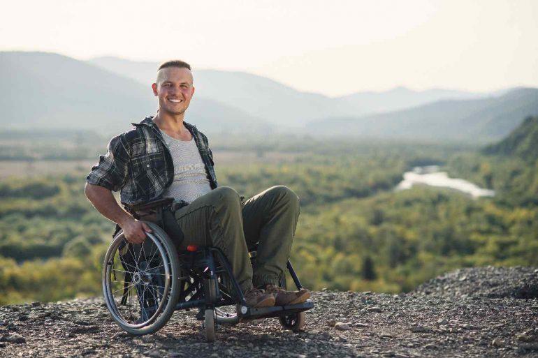 A man in a wheelchair enjoying the wilderness.