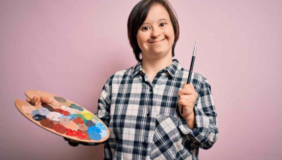 Young down syndrome artist woman holding painter palette and paintbrush over pink background with a happy face standing and smiling with a confident smile showing teeth