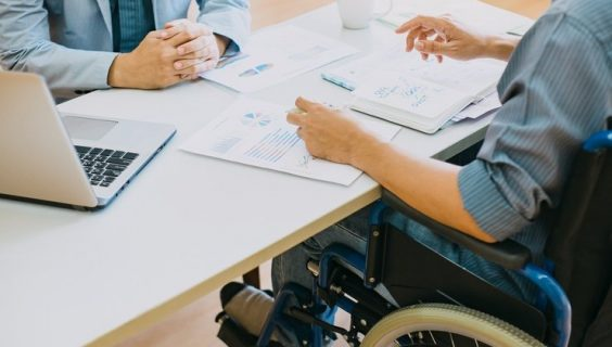 A person in a wheelchair meeting at a table to discuss some papers