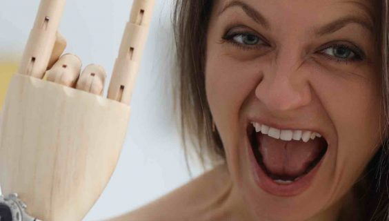 Portrait of crazy female screaming with joy and showing cool gesture with prosthetic and healthy arm.